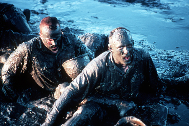"""A U.S. Navy Basic Underwater Demolition/Sea-Air-Land (SEAL) (BUD/S) trainees struggle in a mud pit during a """"hell week"""" exercise. Phase I of BUD/S training concludes with """"hell week,"""" when students' physical, emotional and mental abilities are tested under adverse conditions"""
