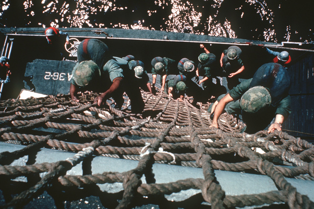 A U.S. Navy Basic Underwater Demolition/Sea-Air-Land (SEAL) (BUD/S) trainees use a debarkation net to climb from a ship into a landing craft, vehicle, personnel (LCVP) during a training exercise