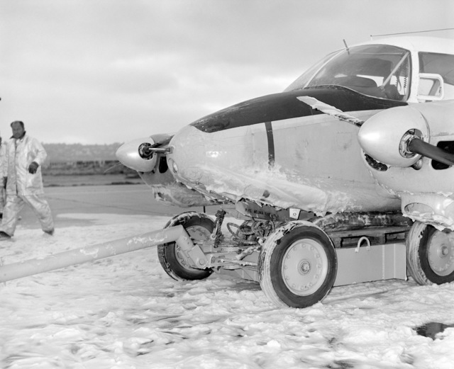 A disabled U-11A Aztec aircraft is towed off the runway at Naval Air Station, North Island. The aircraft crashed after its nose gear failed to operate properly
