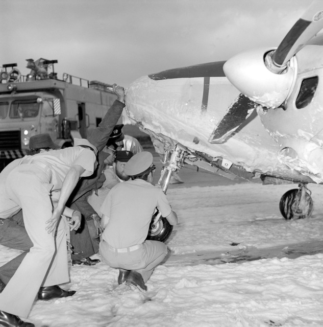 Navy personnel inspect the nose gear on a U-11A Aztec aircraft at Naval Air Station, North Island after it failed to operate causing the aircraft to crash land