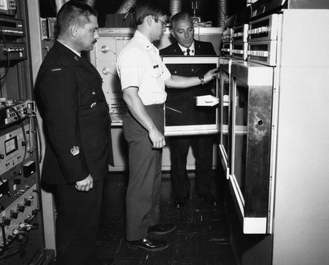 Specialists from the Canadian Air Command, Warrant Officer S. L. Smith, left, and Sergeant R. G. Farquhar, right, receive training in the use of components that control the Air Force Avionics Laboratory's optical properties of orbiting spacecraft (OPOS) telescope
