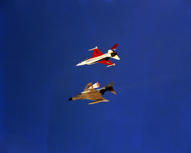 An air-to-air left side view of an F-4 Phantom II aircraft flying in formation with an F-16 Fighting Falcon aircraft. The F-4 is carrying a tow target on its left wing