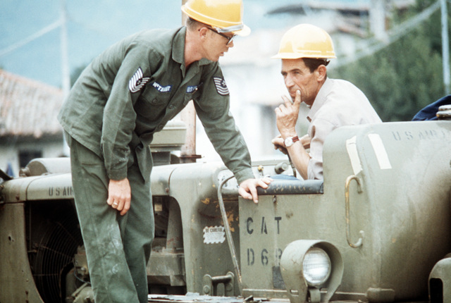 A U.S. Air Force master sergeant from Aviano Air Base, Italy, confers with an Italian worker clearing rubble in clean-up operations after a severe earthquake