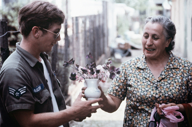 A villager offers an airman from Aviano Air Base, Italy, a vase of flowers to thank him for his help in saving some of her valuables following a severe earthquake