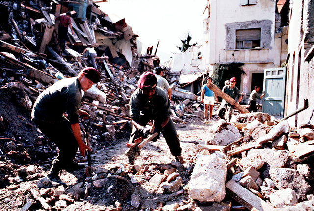 Army paratroopers help to direct the clearing of rubble as clean-up operations get underway following a severe earthquake