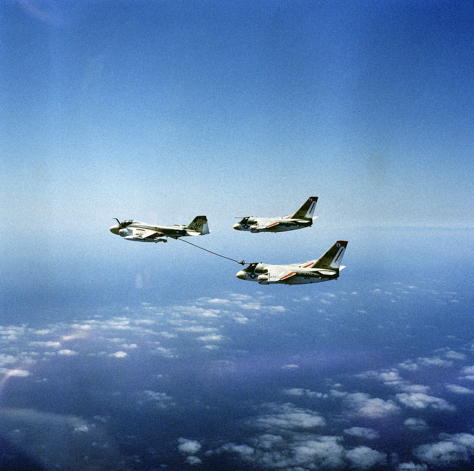 Air-to-air left side view of a KA-6D Intruder tanker aircraft from Medium Attack Squadron 52 (VA-52) (left) refueling two S-3 Viking aircraft from Air Antisubmarine Squadron (VS-33)