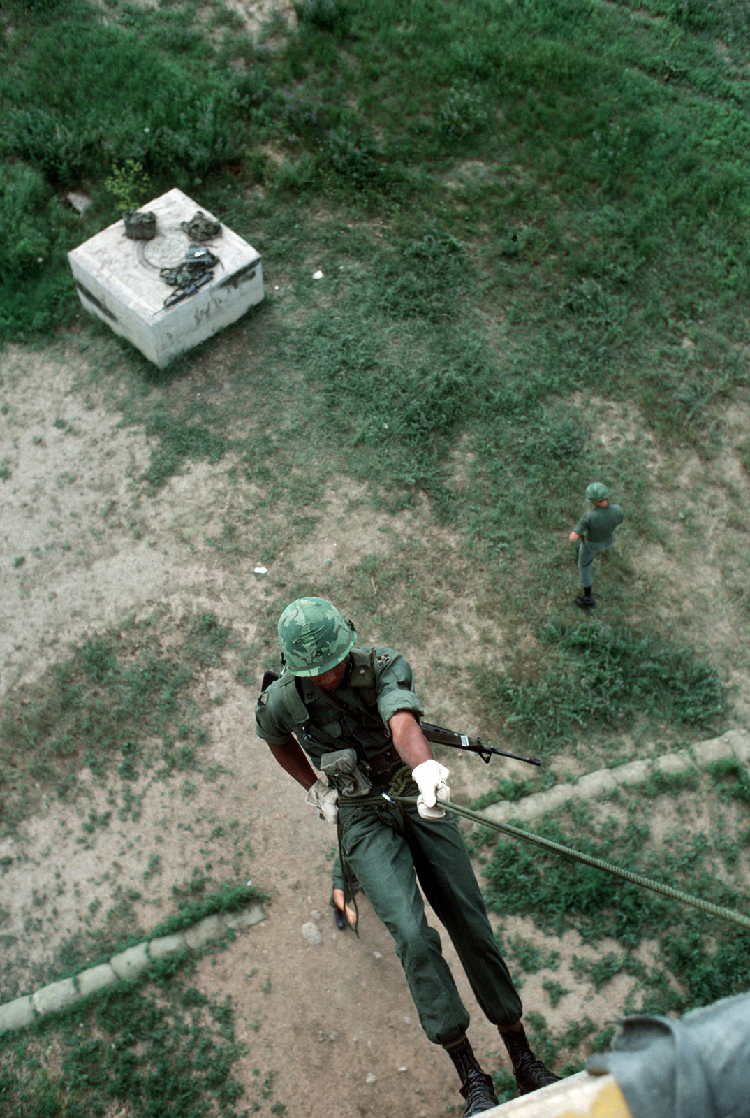 A US Army soldier practices rappelling from a tower during a field training exercise
