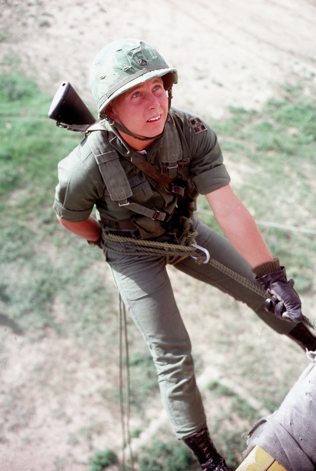 A U.S. Army soldier practices rappelling from a tower during a field training exercise