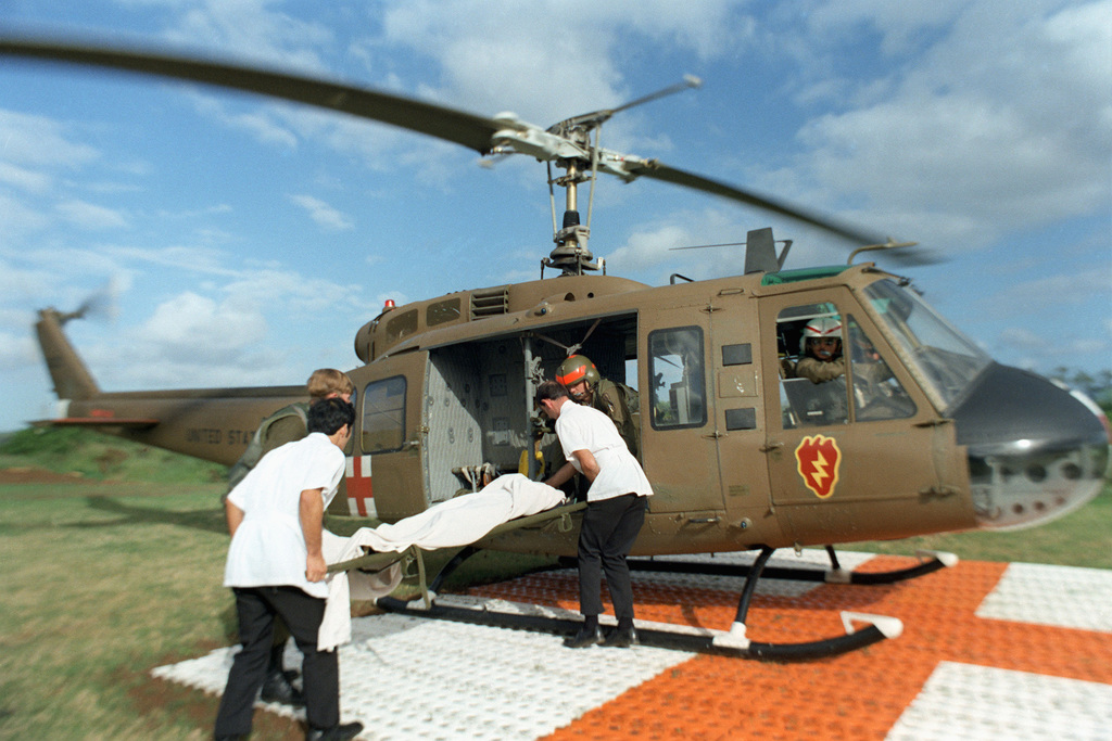 Hospital personnel and US Army medics from the 68th Medical Detachment, 25th Infantry Division, place a patient into a UH-1 Iroquois helicopter for a flight to a hospital in Honolulu