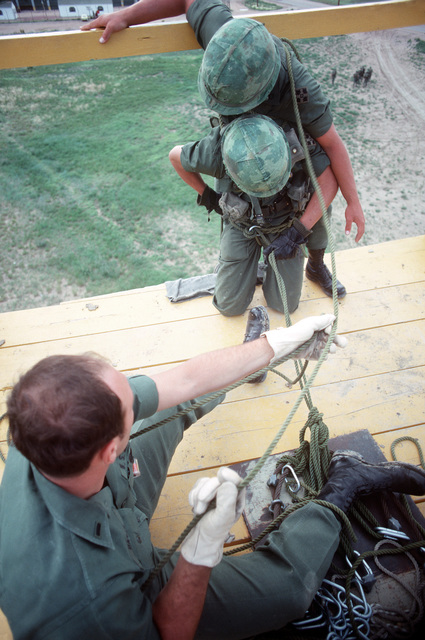 US Army soldiers practice rappelling from a tower during a field training exercise