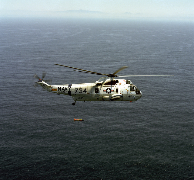 An air-to-air right side view of a Helicopter Anti-submarine Squadron 6 (HS-6) SH-3 Sea King helicopter with ASQ-81 magnetic anomaly detection (MAD) gear suspended below it during training operations off the coast of Southern California