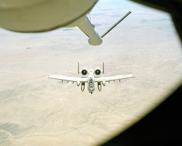 An air-to-air view from a KC-135 Stratotanker aircraft as its boom connects and refuels an A-10A Thunderbolt II aircraft