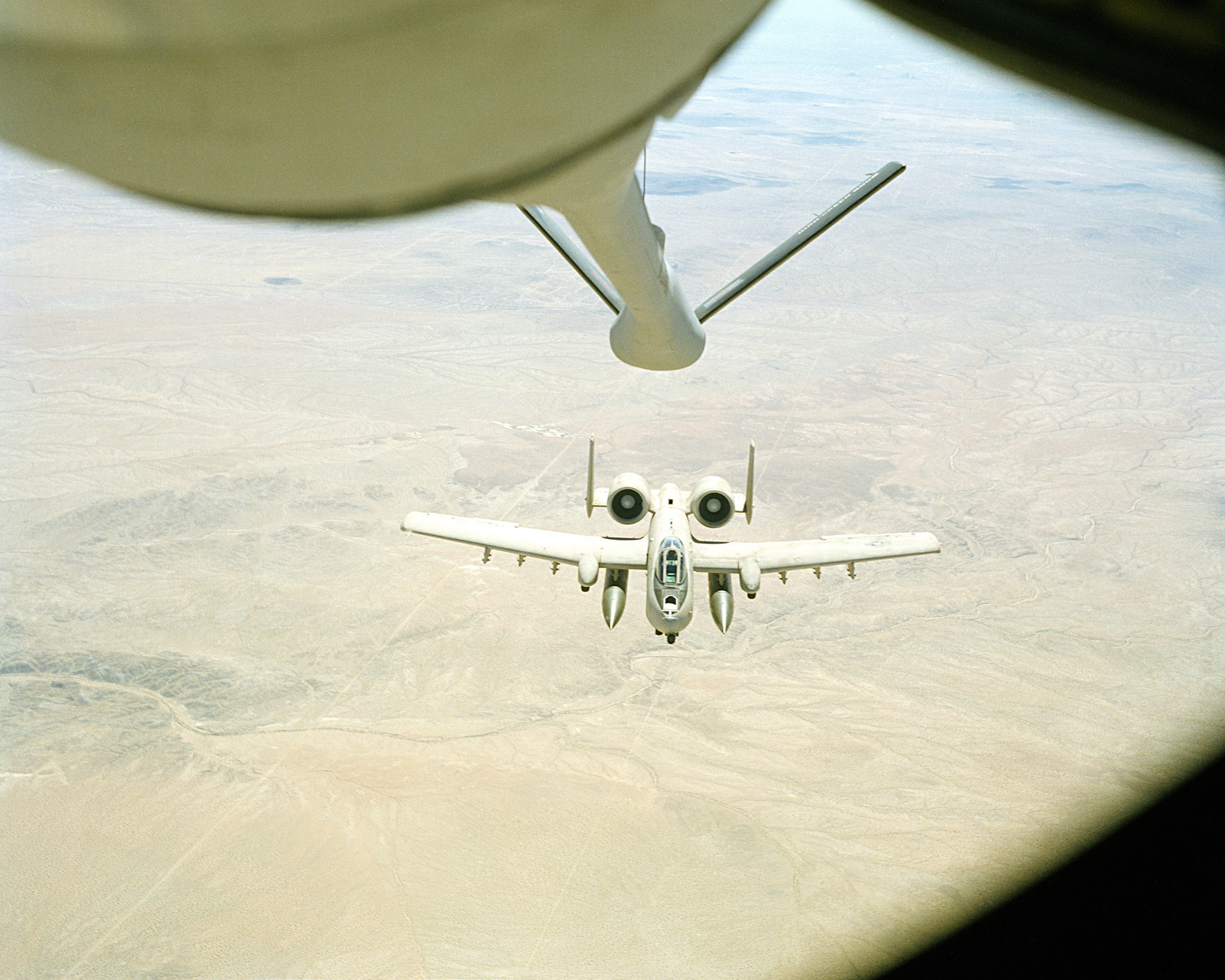 An air-to-air view from a KC-135 Stratotanker aircraft as its boom is lowered to refuel an A-10A Thunderbolt II aircraft, that is coming up to meet the boom