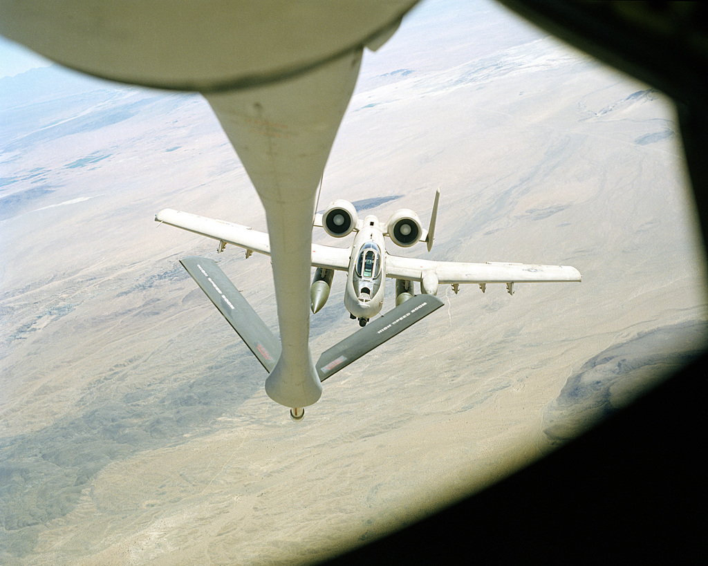 An air-to-air view from a KC-135 Stratotanker aircraft as its boom lowered, as an A-10A Thunderbolt II aircraft comes up line for refueling