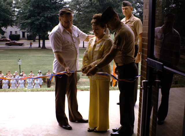 Mrs. Dean L. Bruce is assisted by her husband and GYSGT A. K. Willford, dining facility manger, in cutting the ribbon to official open Bruce Hall. The building was named after their son, PFC Daniel D. Bruce. LGEN Joseph C. Fegan, commanding general, is looking on