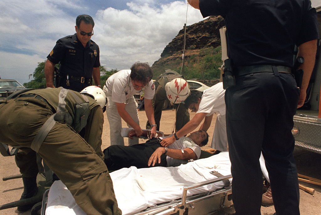 U.S. Army medics from the 68th Medical Detachment, 25th Infantry Division, help Honolulu police officers move a heart attack victim for transfer to a medical evacuation helicopter