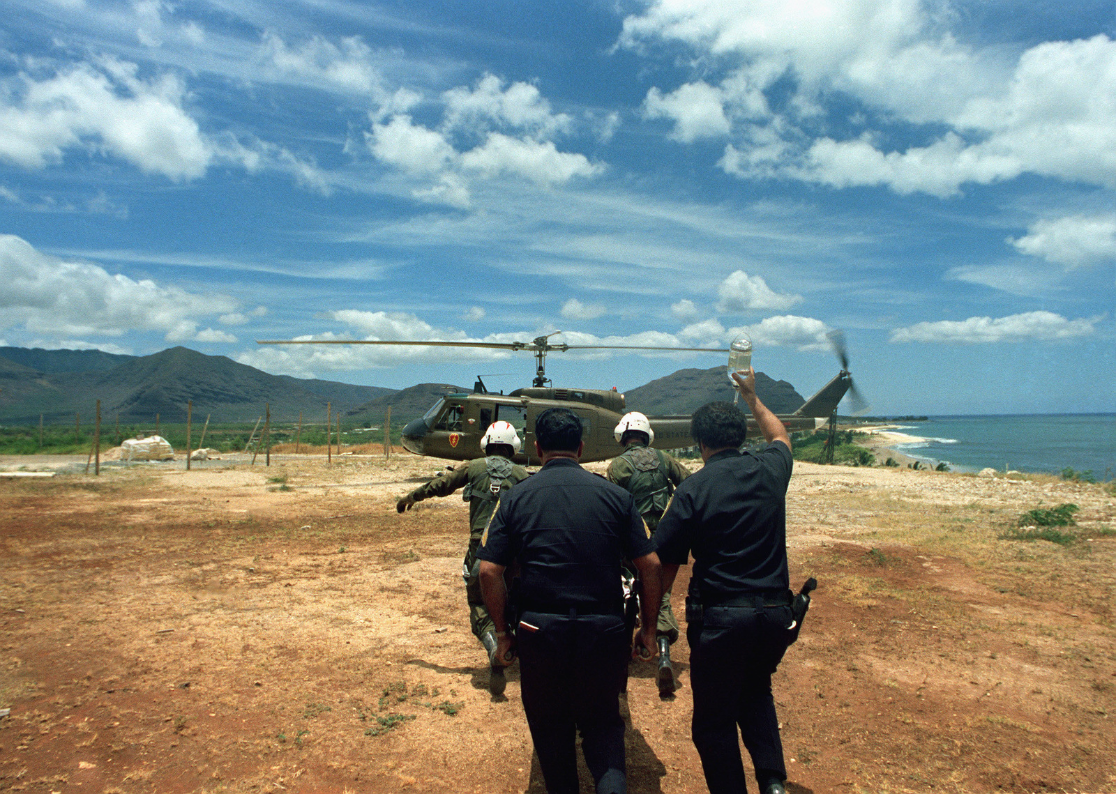 US Army medics from the 68th Medical Detachment, 25th Infantry Division, help Honolulu police officers transfer a a heart attack victim to a UH-1 Iroquois helicopter for a flight to a hospital