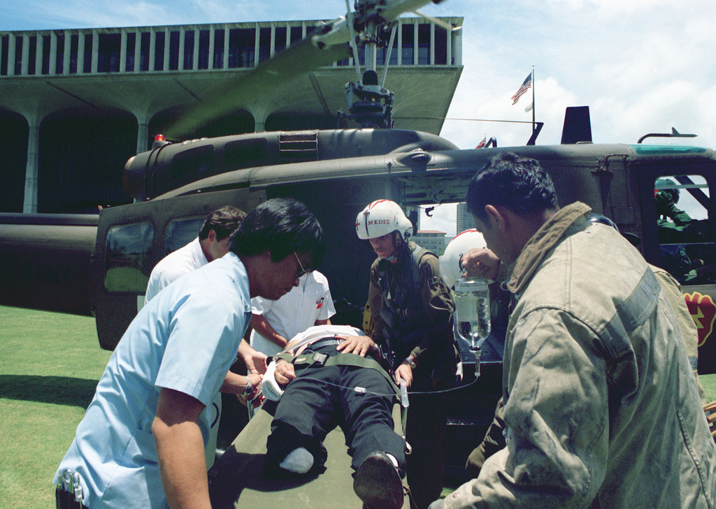 US Army medics from the 68th Medical Detachment, 25th Infantry Division, remove a heart attack victim from a UH-1 Iroquois helicopter after arriving at the hospital