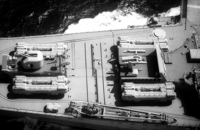 An elevated view of the bow of the Soviet aircraft carrier KIEV (CVHG) showing a 76.2mm/60-caliber anti-aircraft gun, eight SS-N-12 Shaddock missile launch tubes and an SA-N-3 missile launcher. A retracted SA-N-4 missile launcher is under the circular cover plate in the upper left