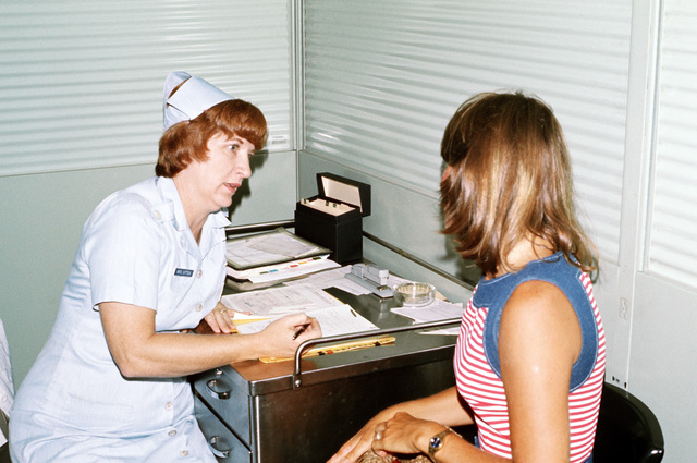 American Red Cross Volunteer Audrey Sitten, screens Meredith Clifton, a dependent wife, prior to her admittance as a patient at Kenner Army Hospital