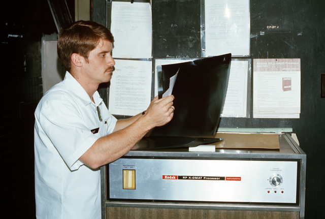 Dale A. May, a civilian X-ray technician, processes X-ray films on a Kodak RP X-Omat Processor at Kenner Army Hospital