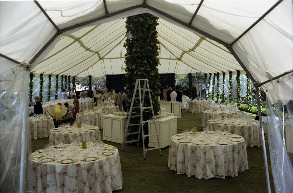 White House Staff Setting Up Tables and Decorations in a Tent on the South Lawn of the White House in Preparation for a State Dinner Honoring Queen Elizabeth II and Prince Philip of Great Britain