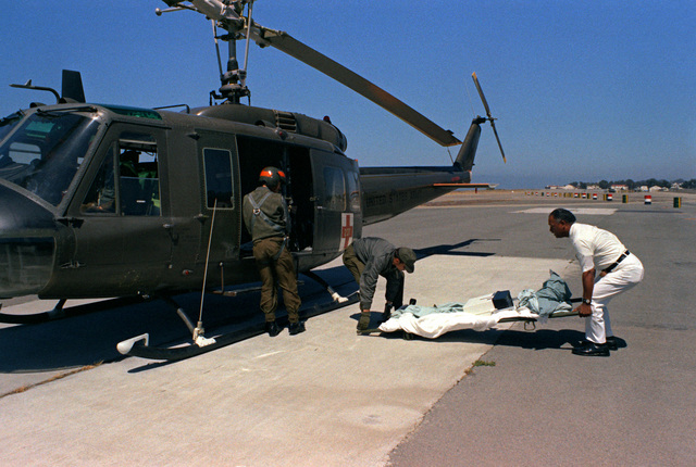 Members of the Army Health Services Command prepare to load an organ transplant a UH-1 Iroquois helicopter for medical airlift to its ultimate destination