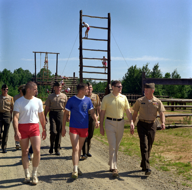 COL D.D. Dean, right, accompanies Assistant Secretary of the Navy G.D. Penisten on a tour of the obstacle course at the Marine Corps Development and Education Command. Walking with them is 2LT G. Wells, left, student company commander, Company C, and CPT J. M. Strickland, second from left