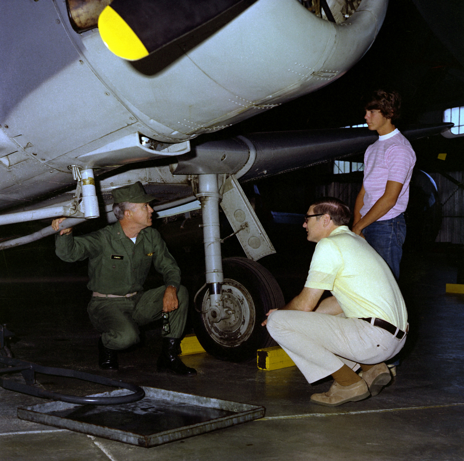 COL T.M. D'Andrea, left, explains an aircraft to Assistant Secretary of the Navy G.D. Penisten and his son, Noel, during their visit to the Marine Corps Air Museum at the Marine Corps Development and Education Command