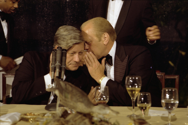President Gerald R. Ford Speaking Directly Into the Ear of Chancellor Helmut Schmidt of the Federal Republic of Germany following the Toasts at a State Dinner Honoring Chancellor Schmidt