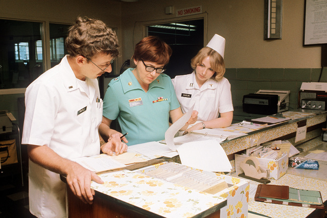 First LT. Robert Tritle, left, registered nurse, confers with MAJ. Claire M. McQuail, center, administrative resident, and CAPT. Linda Shields, registered nurse, on a ward at the Womack Army Hospital