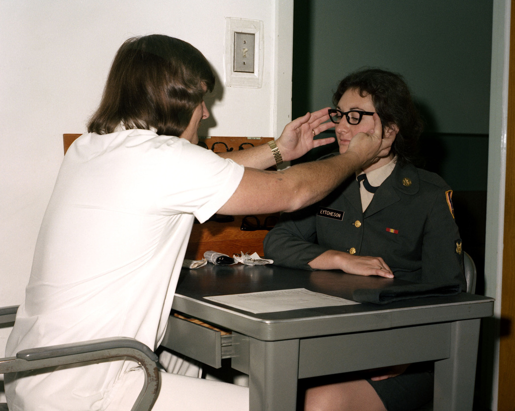 Richard Lowery fits glasses on a patient in the ear, eye, nose, and throat clinic at Darnall Army Hospital