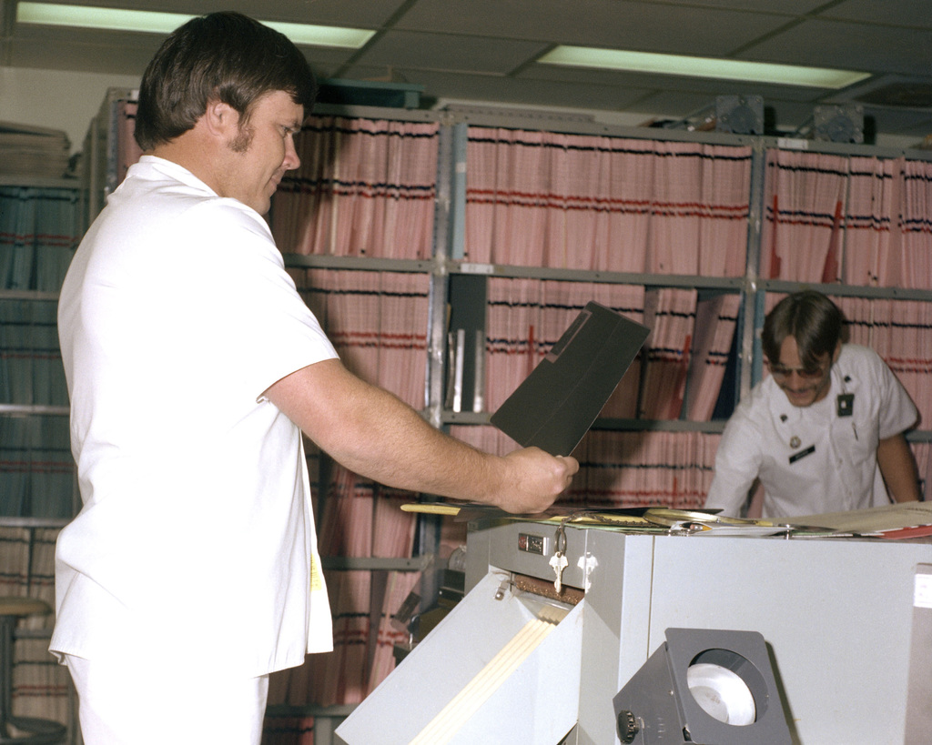 Robert Watts checks X-ray film as it comes off the processor at Darnall Army Hospital