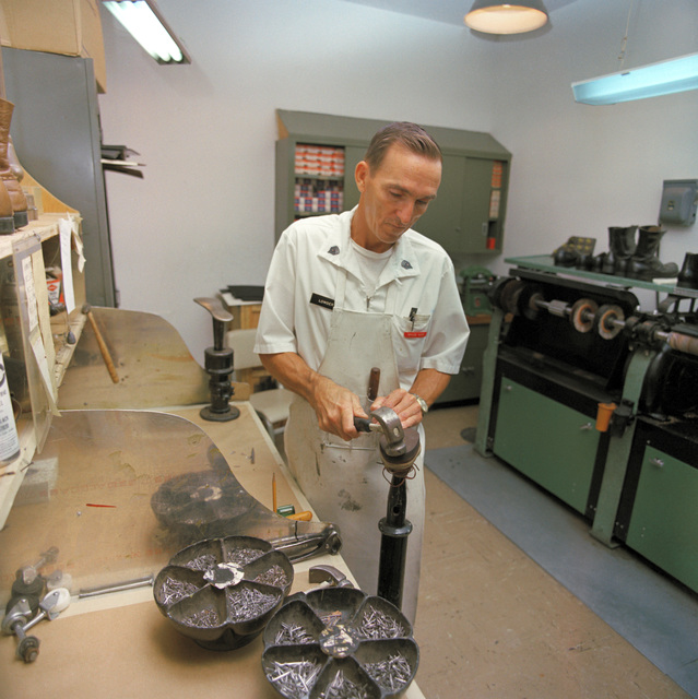 SPECIALIST 6 Earnest G. Lowder drives in the finishing nails on a corrective shoe in the brace shop at Womack Army Hospital