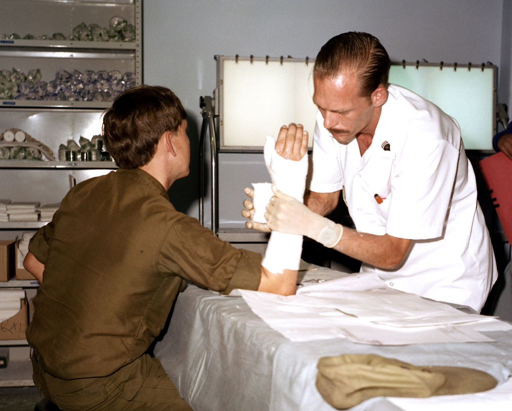 SPECIALIST 6 John Oats applies a short arm cast to a patient in the orthopedic clinic at Darnall Army Hospital