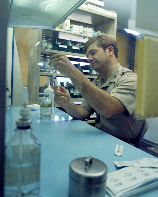 Captain (Dr.) Bruce R. Harrison, working under the laminar flow sterile hood, puts additives in sterile water for intravenous injection in the IV additive section at Womack Army Hospital
