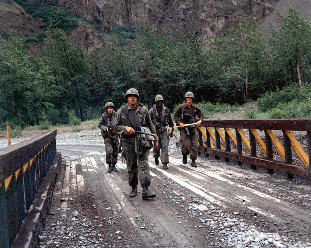 SGT Glenn Southwick, an instructor with the Snow Hawk Fledging Course, 172nd Infantry Brigade, crosses a bridge near the Eklutna glacier with members of Company A, 2nd Battalion, 2nd Infantry, from Fort Lewis, Washington