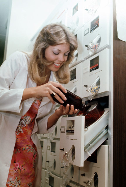 Katherine Sawyer, a civilian intern, fills prescriptions using a Baker Cell at Womack Army Hospital