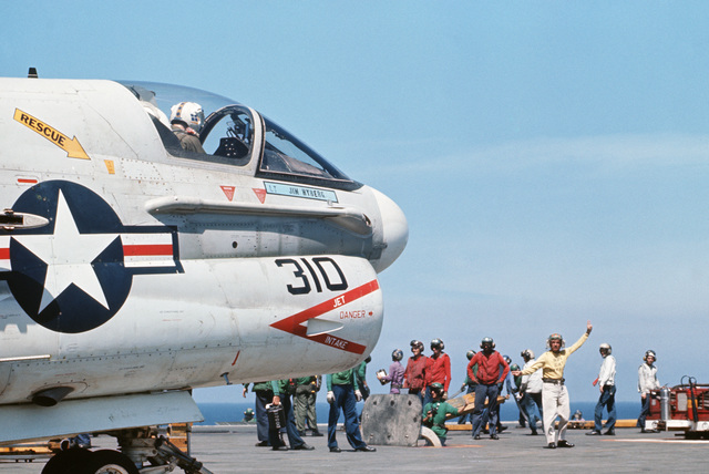The bow catapult officer signals to the pilot of an A-7E Corsair II aircraft during flight operations aboard the aircraft carrier USS AMERICA (CV 66)