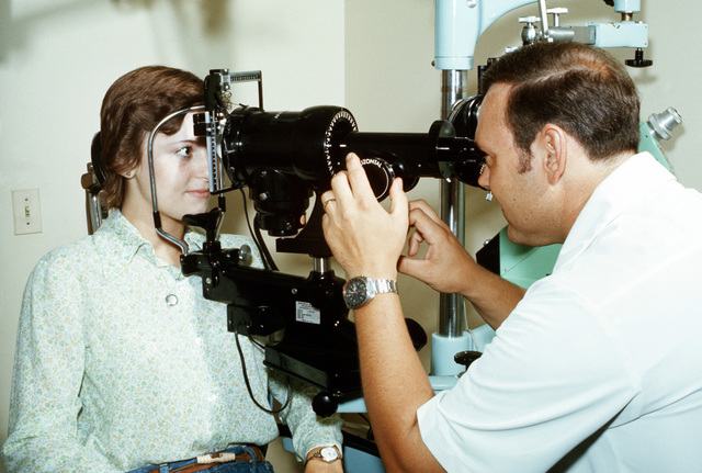 Donna Jean Napier, a dependent, has her eyes checked by Dr. (CPT) R.A. Manchette at the medical department activity (MEDDAC) health services building. He is using an Ophthalmoscope
