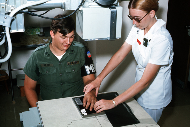 SGT Glen McCoy, non-commissioned officer in charge of post detention, 204th Military Police Company, has his hand X-rayed by SPC Carol S. Voelker, an X-ray technician at the medical department activity (MEDDAC) health services complex