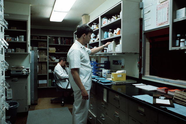 SPEC 5 Patrick G. Marshall, a pharmacy specialists, surveys a shelf as 1LT Martin Beasley, the pharmacy officer, talks on the phone at the medical department activity (MEDDAC) health services complex