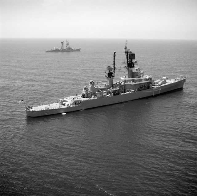 An aerial starboard quarter view of the guided missile cruiser USS HALSEY (CG 23) anchored off the coast of Southern California. The guided missile destroyer USS DECATUR (DDG 31) is visible in the background