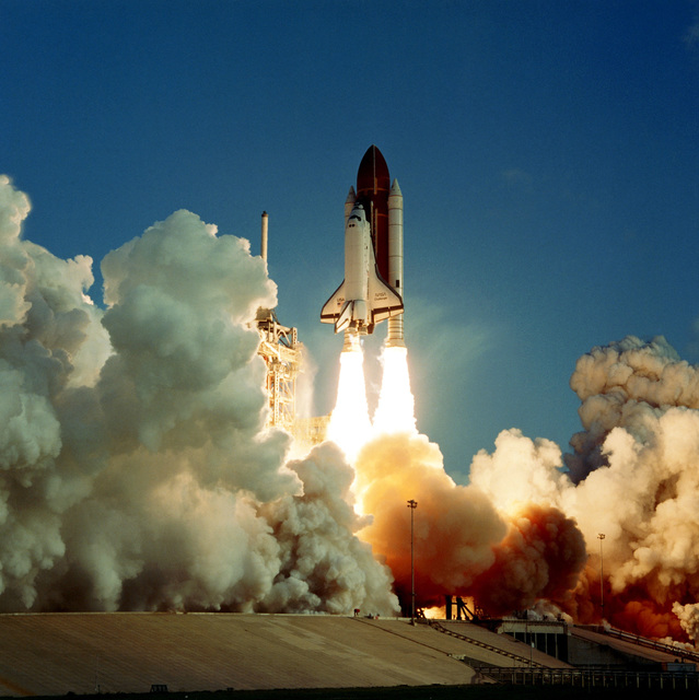 A ground-to-air view of the space shuttle Challenger during liftoff from launch complex 39A at 7:33 a.m. EDT. Aboard the Challenger for the seventh launch of the Space Transportation System are CMDR Bob Crippen, pilot Frederick H. Hauck, and mission specialists Sally Ride, John M. Fabian and Dr. Norman Thagard