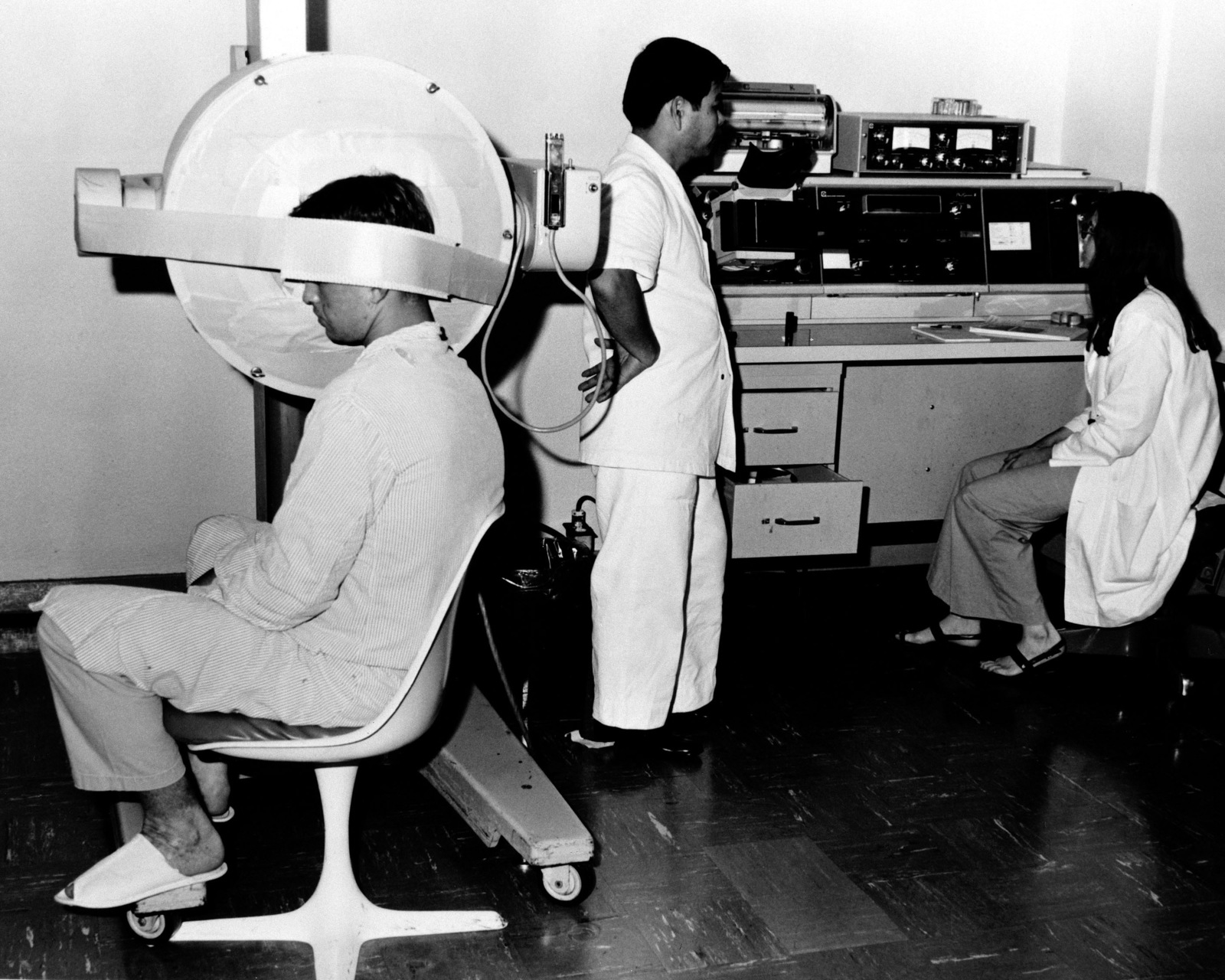 A patient undergoes a brain scan on the Scintillation camera to detect a tumor, blood flow and placement, abscesses, etc., in the Radio Isotope Clinic at the U.S. Army Hospital, Camp Kuwae