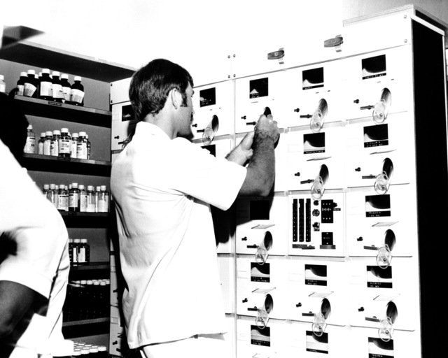 A pharmacy specialist fills prescriptions using the Baker Cell Medication Counting and Dispensing Unit at the U.S. Army Hospital, Camp Kuwae