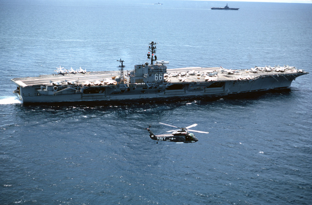 A Helicopter Combat Support Squadron 2 (HC-2) UH-2 Seasprite helicopter flies off the starboard side of the aircraft carrier USS AMERICA (CV 66) while the ship is underway.  An unidentified aircraft carrier is in the background