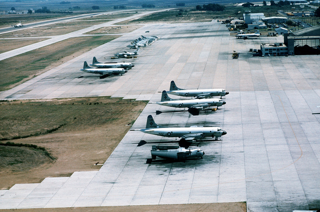 An aerial view of a U.S. Navy C-2A Greyhound, front, three P-3B Orion and two EP-3B Orion aircraft parked on the flight line
