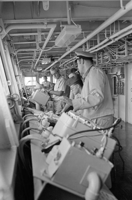 Rear Admiral Frederick F. Palmer, center, Commander Amphibious Group Two, talks to crewman on the bridge of the amphibious command ship USS MOUNT WHITNEY (LCC 20) while en route to participate in the allied Exercise TEAM WORK '76. The MOUNT WHITNEY is serving as flagship during the exercise scheduled for September 15-24