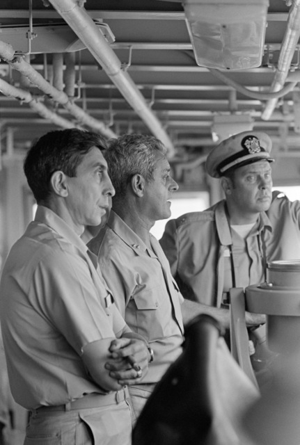 Rear Admiral Frederick F. Palmer, Commander, Amphibious Group Two, center, talks to crewmen on the bridge of the amphibious command ship USS MOUNT WHITNEY (LCC 20) while en route to participate in allied Exercise TEAM WORK '76. The MOUNT WHITNEY is serving as flagship during the exercise is scheduled for September 15-24